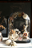 Vintage ornaments and delicate wreath of flowers against glass cover