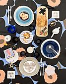 Gedeckter Tisch mit buntem Geschirr auf gemusterter Tischdecke