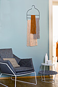 Bohemian-style wall hanging of woollen tassels above modern armchair