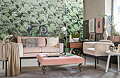Furniture with pink and beige upholstery against jungle-patterned wallpaper