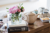 Pfingsrosen, Bücher und Kaffeegeschirr auf dem Couchtisch