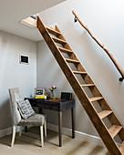 Schreibtisch und Polsterstuhl unter der Treppenleiter