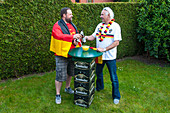Two German fans stood at tall table made from beer crates in garden
