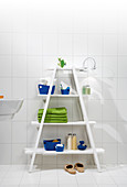Blue and green accessories on white ladder shelves in bathroom
