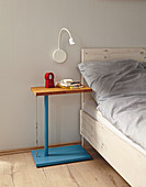 Blue, DIY side table with bamboo top and steel cable next to bed