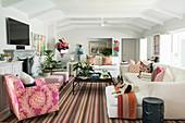 Gestreifter Teppich im weißen Wohnzimmer mit bunten Accessoires