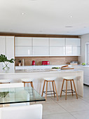 White modern kitchen with wooden elements and red accents provided by electrical appliances