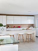 Rote Elektrogeräte als Farbakzent in moderner weißer Küche mit Holz