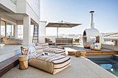 Floor cushions next to pool on roof terrace with lounge area and wood-fired oven
