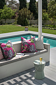 Scatter cushions and seat cushions on outdoor sofa on terrace next to pool