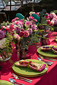 Vases of flowers decorating table set with green plates