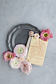 Vintage invitation card and pink flowers on pewter plate
