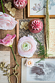 Pink flowers, vintage cards, antique photos and strawberry cupcakes on wooden table