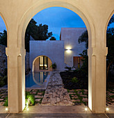 View through arch into courtyard with pool at twilight