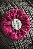 Cushion with knitted cover and knitted flower