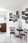 Pictures with black frames on walls of vintage-style seating area
