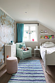 Child's bedroom in delicate shades with sloping ceiling