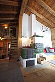 Kachelofen in hohem Wohnraum mit Holzdecke und Treppenaufgang