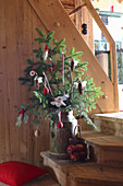 Conifer branches in old milk churn decorated with handmade pine-cone angels