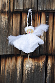 Handmade angel in white dress hung on wooden wall