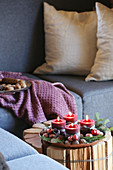 Advent candles in dish on side table handmade from logs