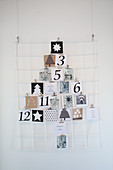 Christmas cards arranged in the shape of a Christmas tree on wire memo board