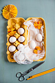 White eggs, muslin and yellow paper rosettes in yellow egg box