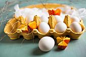 weiße Eier, Mulltuch und gelbe Papierrosetten in gelbem Eierkarton