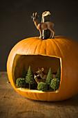 Miniaturwald mit Tierfiguren in einem Kürbis