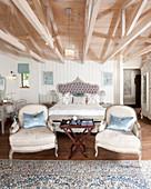 Doppelbett und zwei Sesseln in elegantem Schlafzimmer mit Dachkonstruktion aus Holz