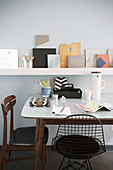 Table and various chairs in front of floating shelf on wall