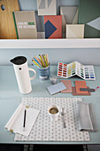 Thermos flask, cup of coffee, writing utensils and colour chart on desk