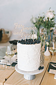 Tall cake topped with blueberries and lettering