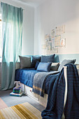 Collage of pictures above bed with various blue scatter cushions