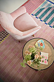 Pink armchair and side table on colourful rug