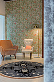 Two retro armchairs on round rug against floral wallpaper
