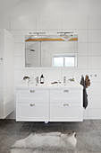 White washstand below wall-mounted mirror in white bathroom