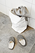 Slippers and laundry bag in bathroom