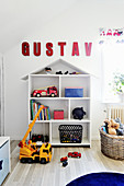 Name written in red letters above house-shaped shelving in child's bedroom