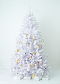 Artificial white Christmas tree with pastries and balls as jewelry