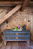 Flower arrangement on top of farmhouse trunk against wooden wall