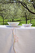 Crockery and handmade tablecloth with cherry blossom patterns on table below flowering cherry tree in garden