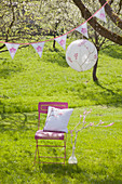 Romantic seat below lantern and bunting on flowering cherry tree:handmade cushion on chair next to branch wound with white yarn and decorated with crocheted flowers