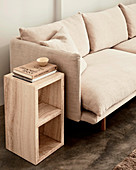 Side table made of wood next to an upholstered couch with a sand-colored cover