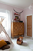 Old cabinet with inlaid veneer doors in vintage-style child's bedroom