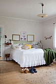 Bed with valance in vintage-style bedroom with board floor
