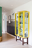 Yellow display cabinet in hallway with wall painted in three shades