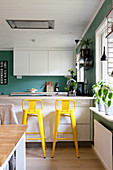 Yellow bar stools at counter in open-plan kitchen