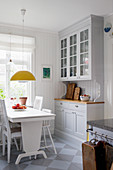Pale grey dresser, white wooden table and chairs in kitchen-dining room
