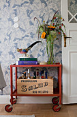 Vintage serving trolley against patterned wallpaper next to open double door painted white